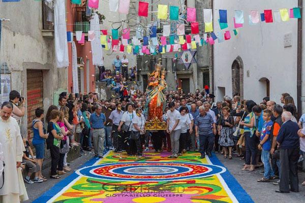 I fedeli realizzano un tappeto multicolore che la Madonna calpesterà per prima,